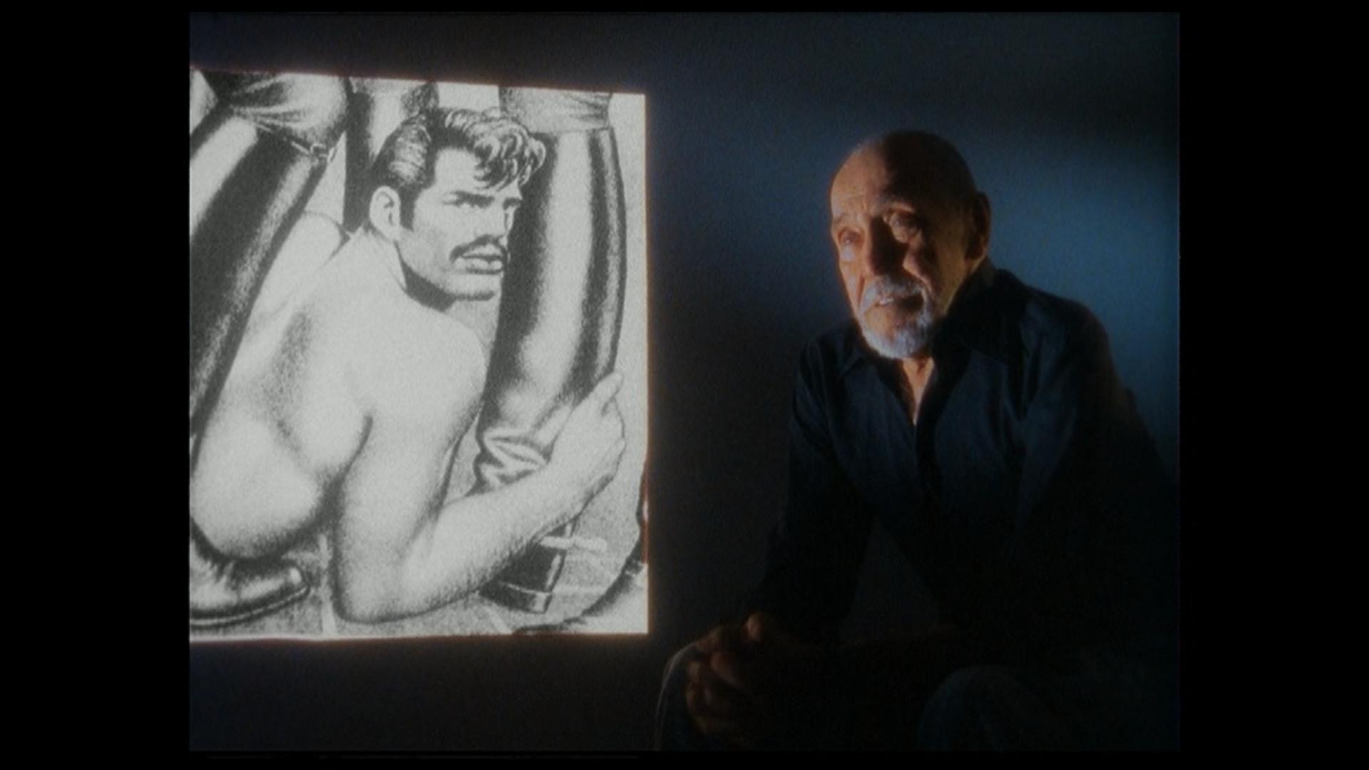 Kuvakaappaus dokumentista Tom of Finland Daddy and the muscle academy: Touko Laaksonen taustallaan piirtämän kuva miehestä nahkasaappaiden keskellä